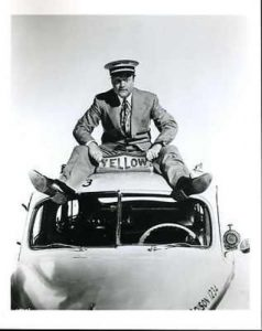 """Publicity photo from """"The Yellow Cab Man"""" - Red Skelton riding on top of the yellow cab"""